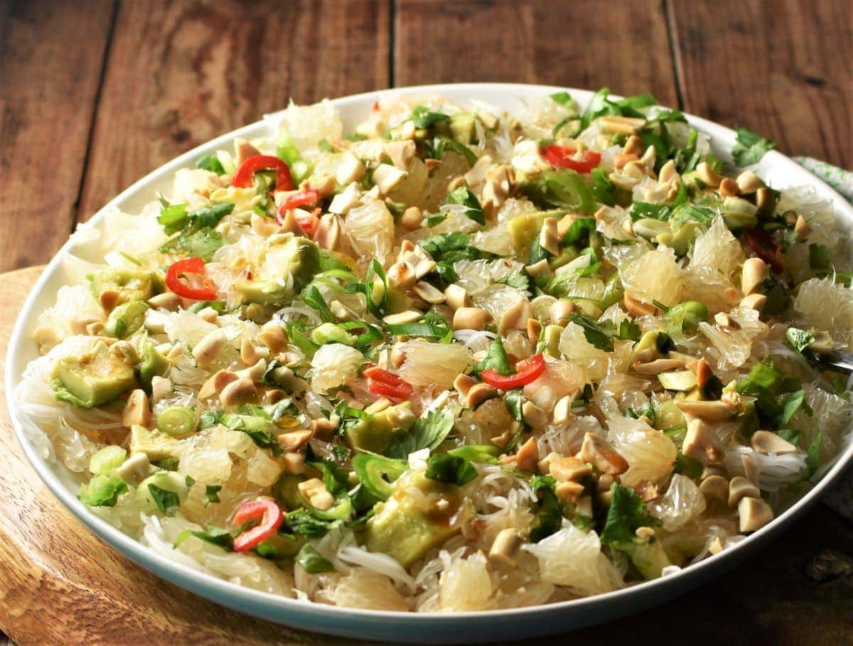 Side view of pomelo salad with noodles on large plate.