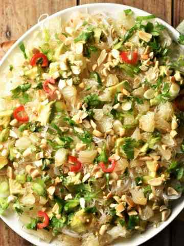 Top down view of pomelo salad with noodles, avocado and herbs on white plate.