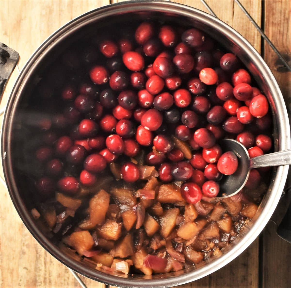 Cooking cranberries with apples and spices in pot.