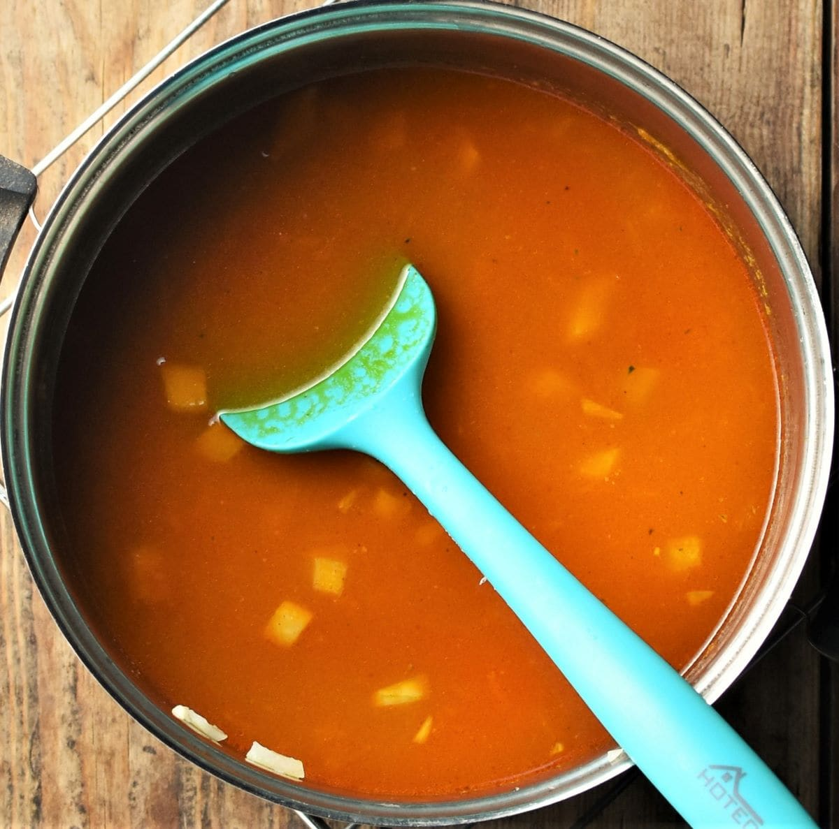 Cooking dhal in saucepan with green spoon.