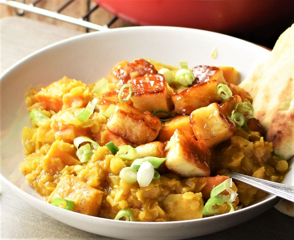 Close-up side view of sweet potato dahl with halloumi in white bowl.