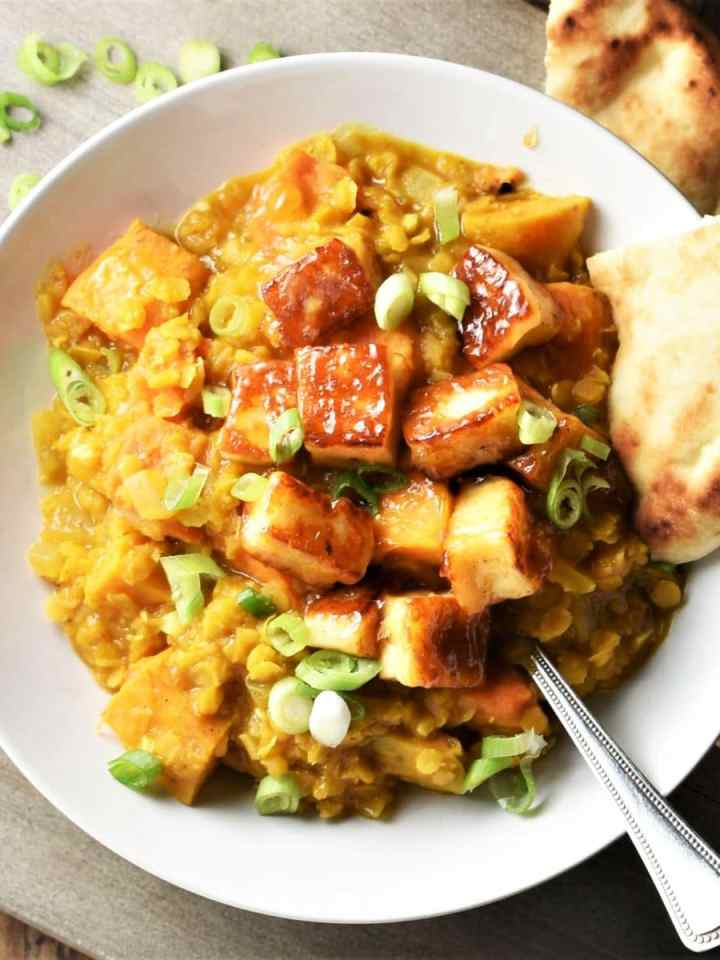 Top down view of sweet potato dhal with fried halloumi cubes in white bowl with naan and spoon.