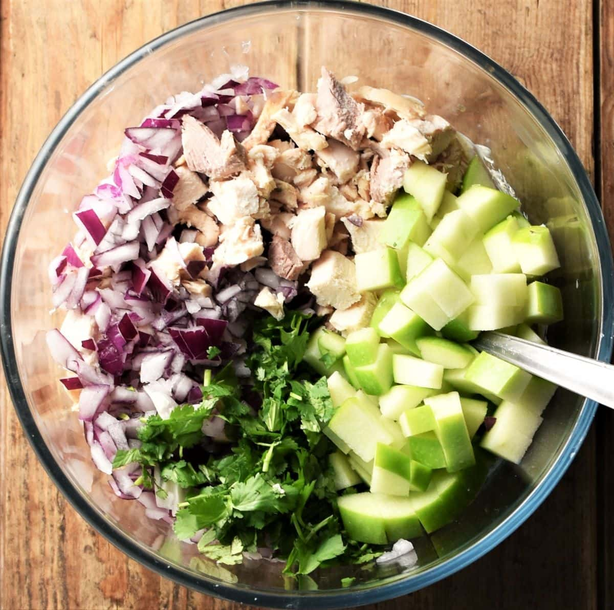 Chopped turkey, red onion, fresh herbs and apple in mixing bowl with spoon.