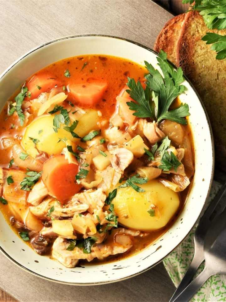 Chicken and potato stew in bowl with vegetables and parsley.