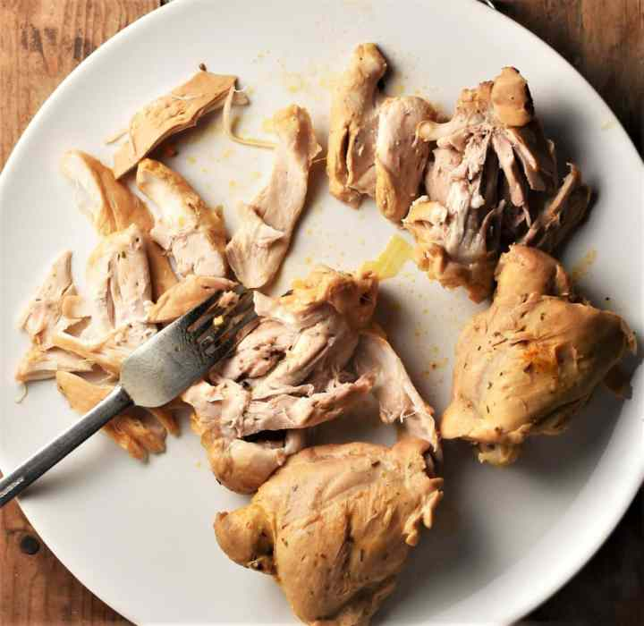 Shredding cooked chicken thighs with fork on top of plate.