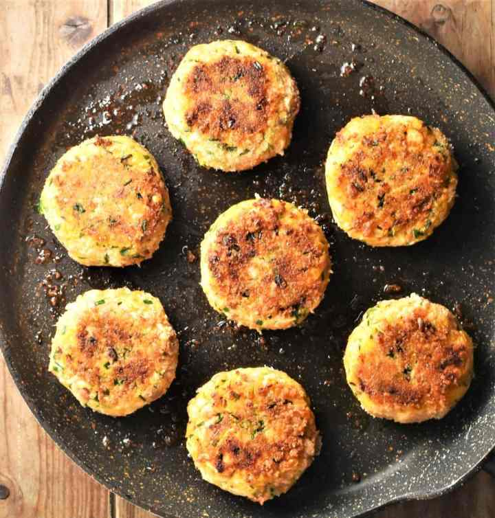 Lightly browned fish cakes on top of frying pan.