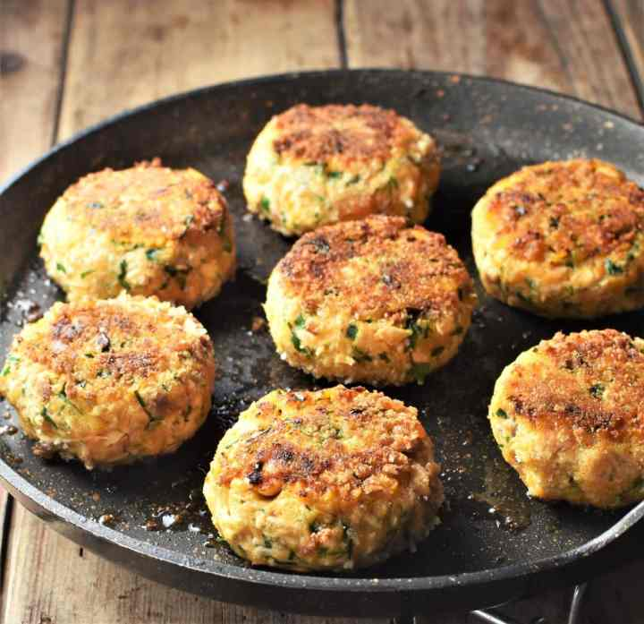 Side view of lightly browned sweet potato fish cakes in large pan.