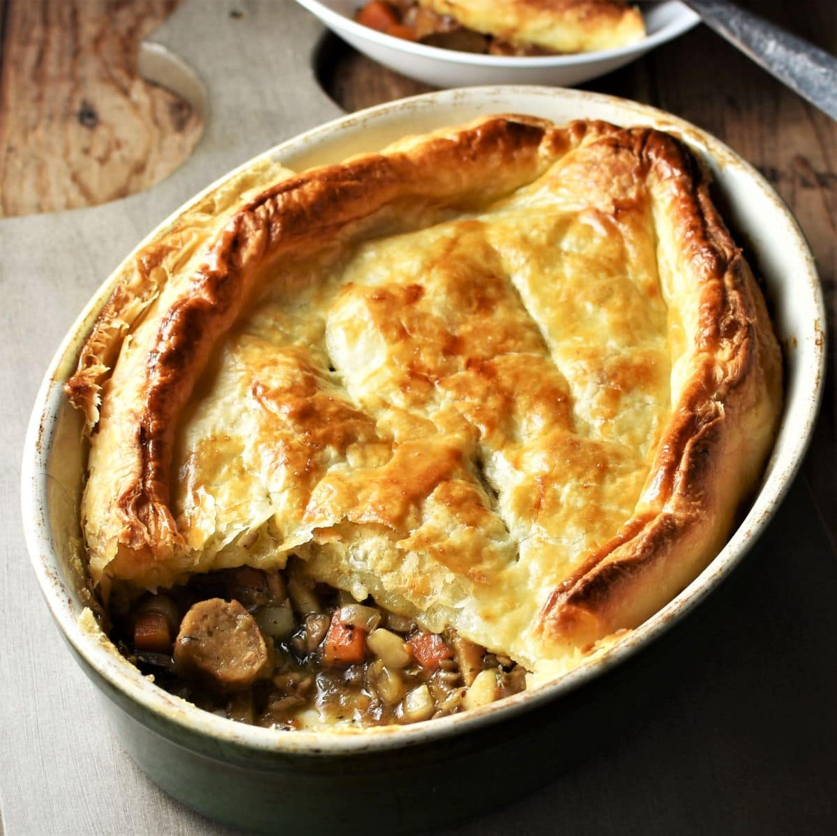 Side view of sausage pie with puff pastry in oval dish.