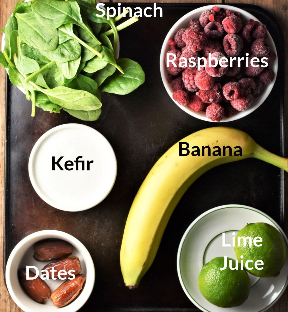 Ingredients for making spinach and raspberry smoothie in individual dishes.