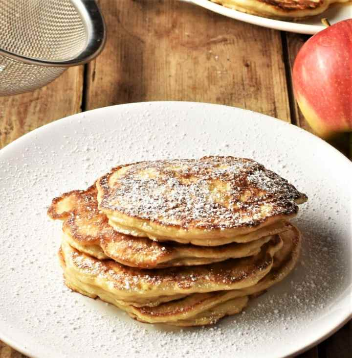Pancakes dusted with powdered sugar stacked on top of large plate.