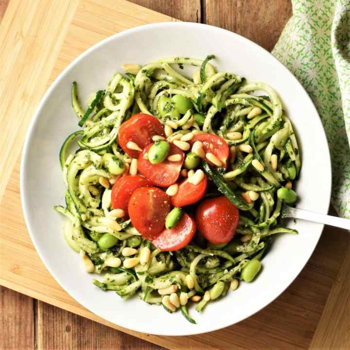 Pesto zoodles salad with cherry tomatoes and beans in white bowl with fork.