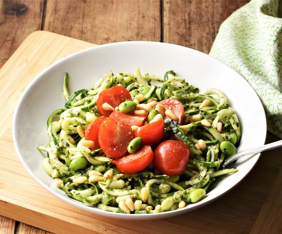Zoodles with pesto, beans and cherry tomatoes in white bowl with fork.