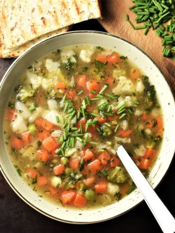 Chunky vegetable soup in green bowl with spoon, fresh chives and grilled bread in background.