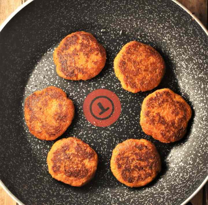 Frying sweet potato fritters in large pan.