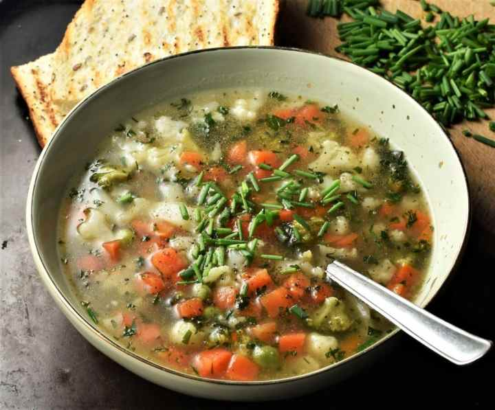 Side view of vegetable soup in green bowl with spoon and herbs in background.