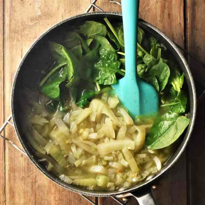 Adding spinach to chunky fennel soup in large pot with blue spoon.