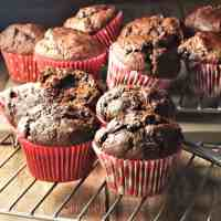 Side view of healthy chocolate muffins in red cases on top of rack.