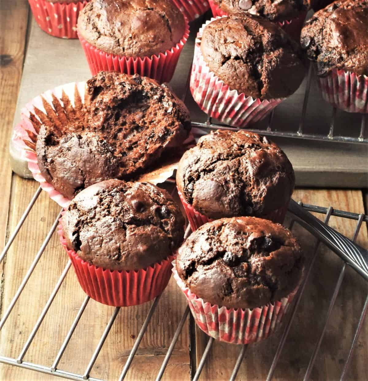 Chocolate muffins in red paper liners on top of rack and board.