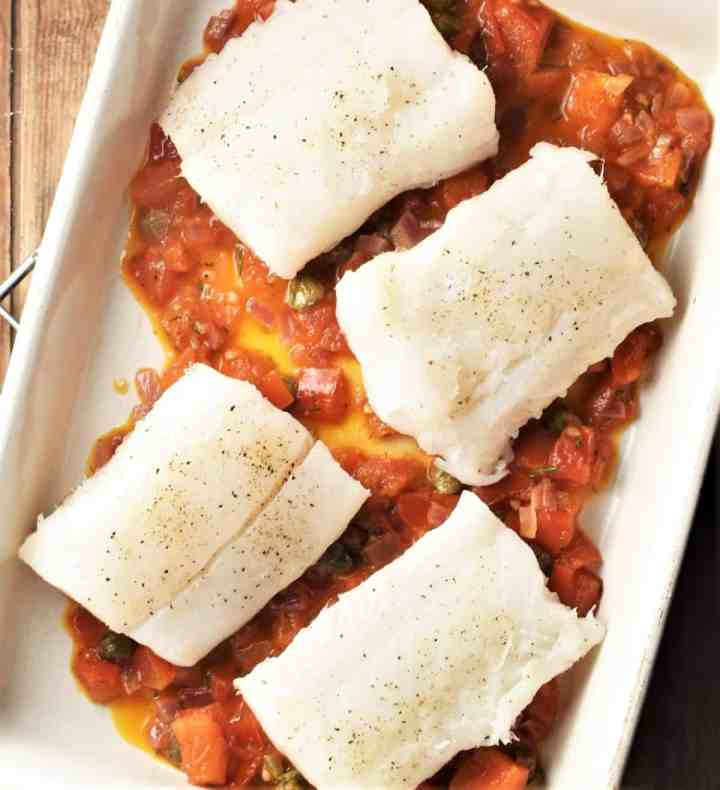 4 pieces of white fish on top of tomato sauce in rectangular dish.