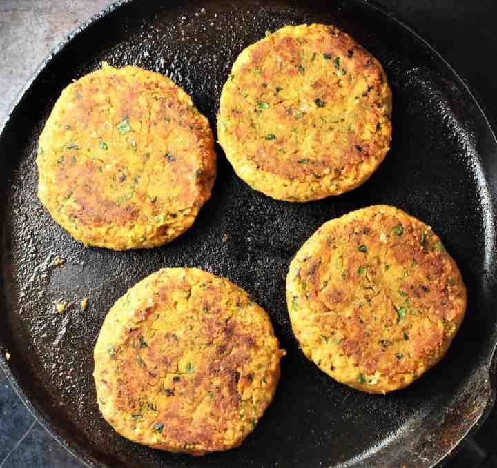Frying 4 sweet potato burgers in large pan.