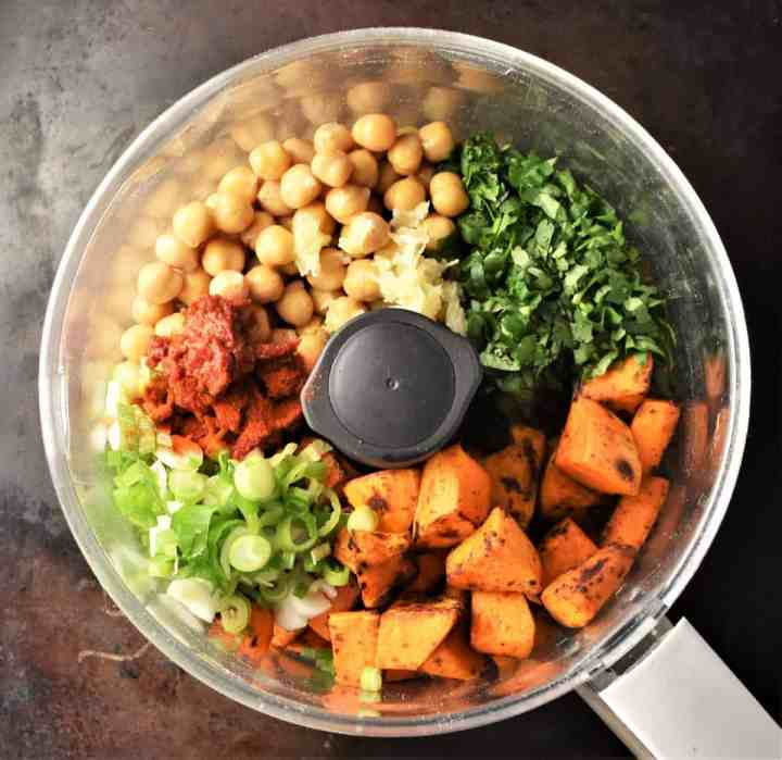 Chunks of sweet potato, chickpeas and herbs in blender bowl.