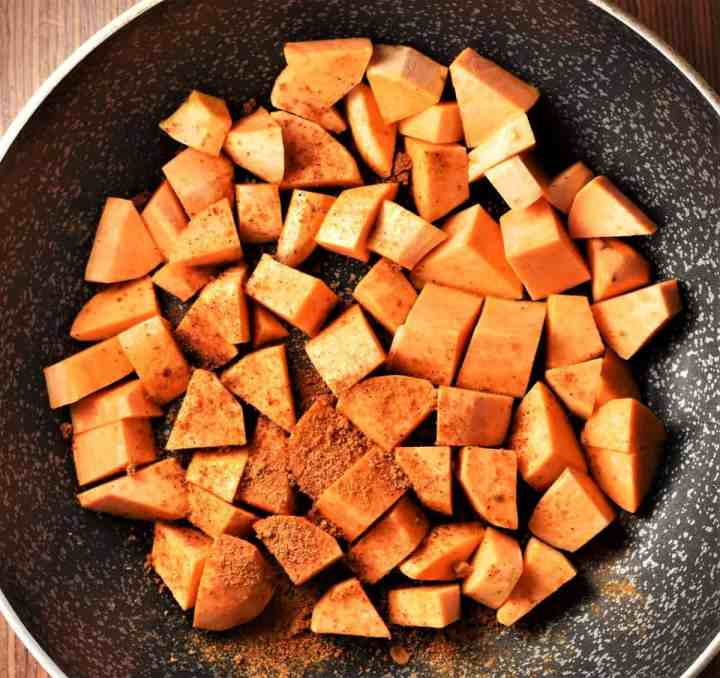 Sweet potato cubes with spices in large pan.