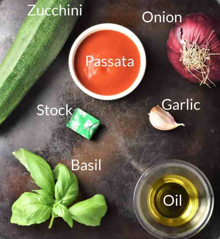 Ingredients for making zucchini tomato soup recipe on top of metal surface.