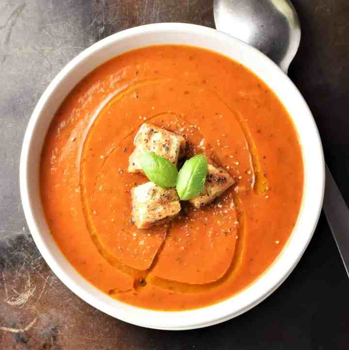 Top down view of creamy tomato zucchini soup with croutons and spoon in background.