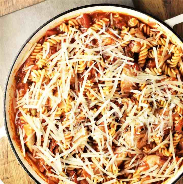 Chicken pasta bake with grated cheese in large shallow dish.