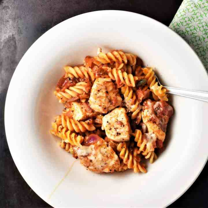 Chicken and pasta with tomato sauce in white dish.
