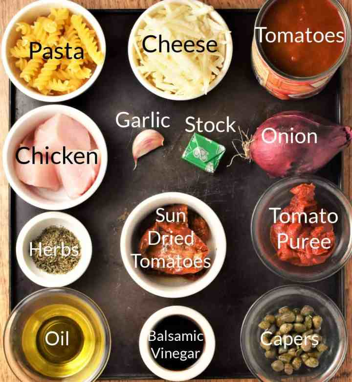 Ingredients for making tomato chicken pasta bake in individual dishes.