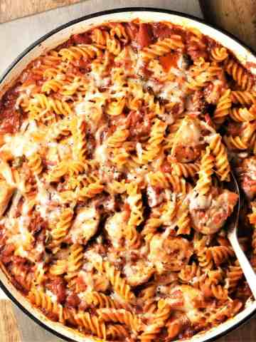 Top down view of chicken tomato pasta bake with spoon in large round dish.