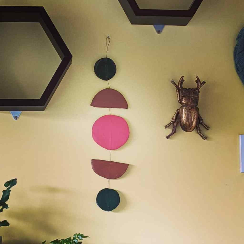 Gold beetle on wall. Wall Hanging in green, brown and pink with a circle, half moon and smaller circle shapes