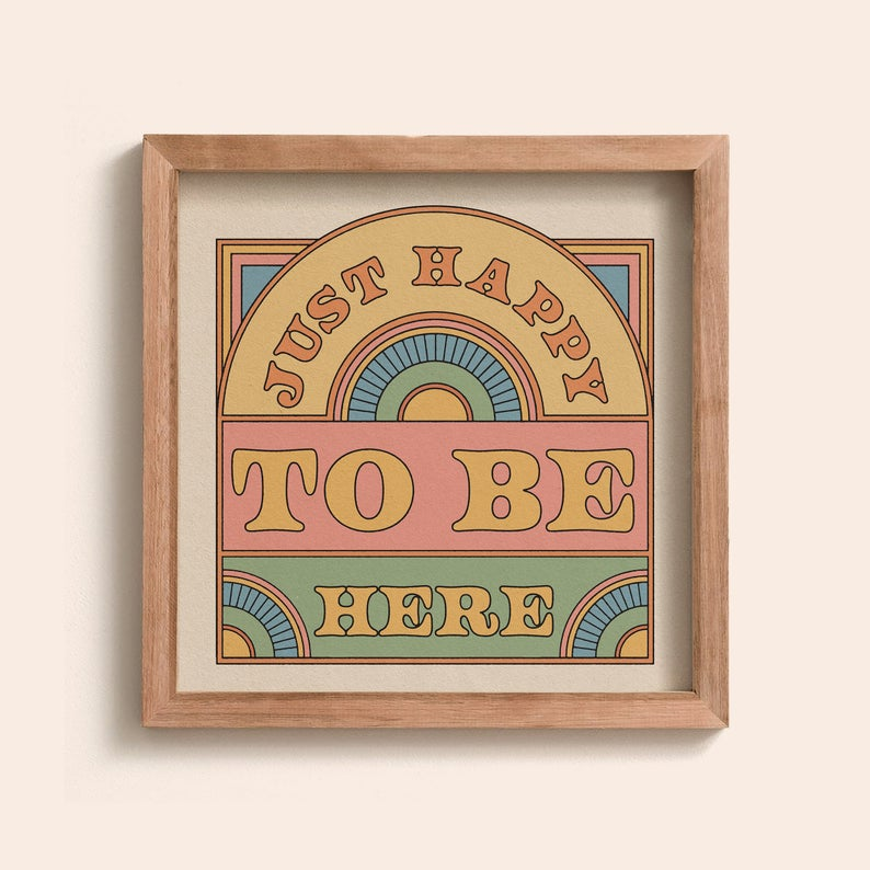 Wooden framed picture on a white wall. Just happy to be here is written in chunky font with a curved top and block design. Thec olours are muted pastels with a 70s vibe.