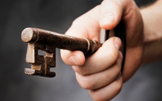 Man holding a big antique key in his hand. Very short depth-of-field.