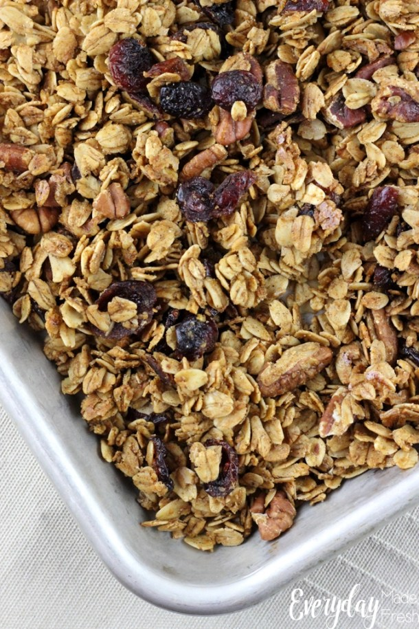 Metal sheet pan with fresh gingerbread granola laid out across it. Clusters of oats, cranberries, and pecans.