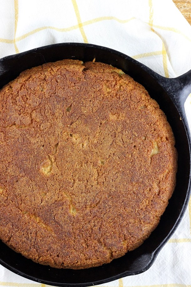 Unsliced pan of corn bread in a cast iron skillet.