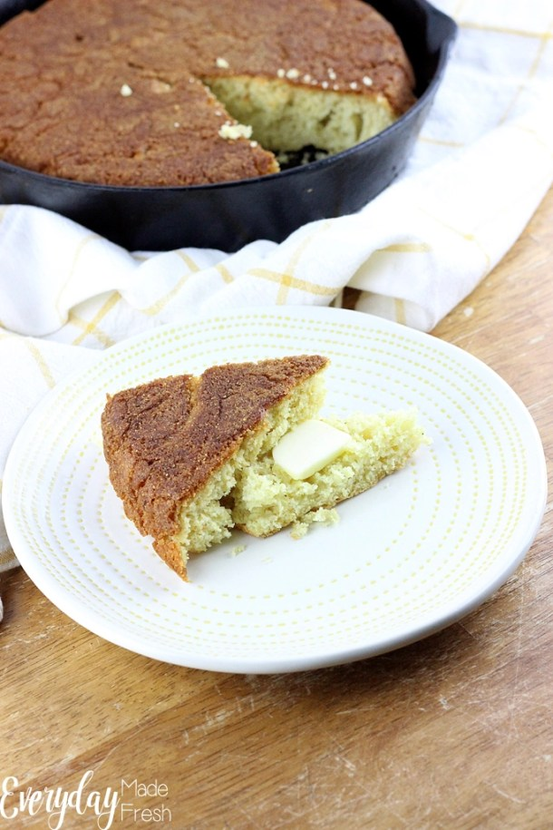 In the front is a plate with a slice of corn bread, split in half with butter melting on it. In the back is a cast iron skillet with corn bread, and a slice missing.