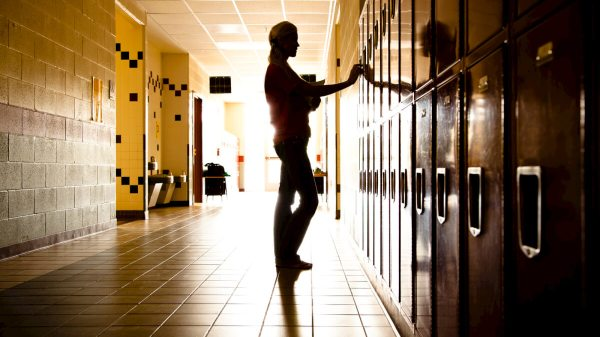 Silhouette of Student in hallway by lockers