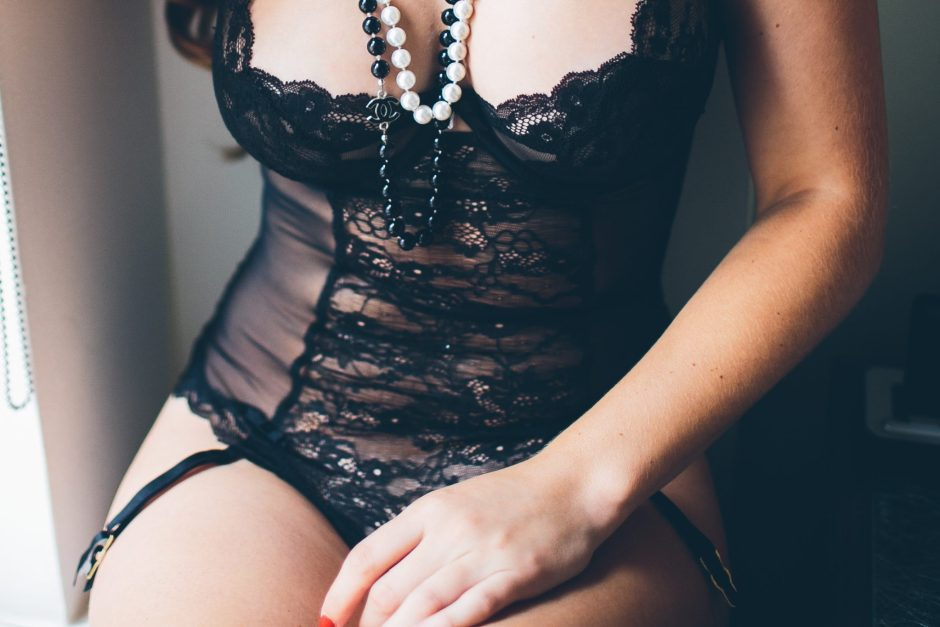 An up close shot of a woman wearing lingerie and a beaded necklace