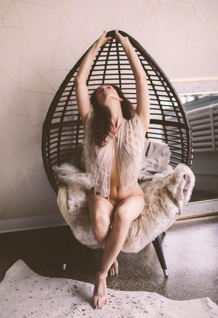 A nude woman posing provocatively on a wicker chair