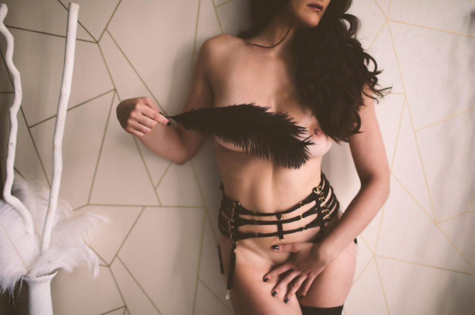 Posing with a feather prop at a boudoir session