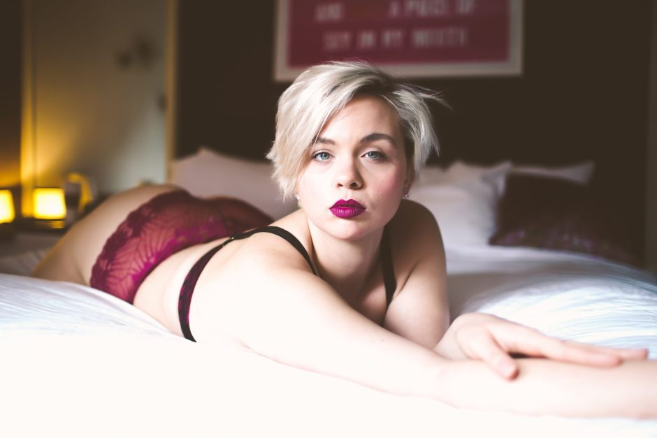 A sexy model wearing crimson lipstick and lingerie