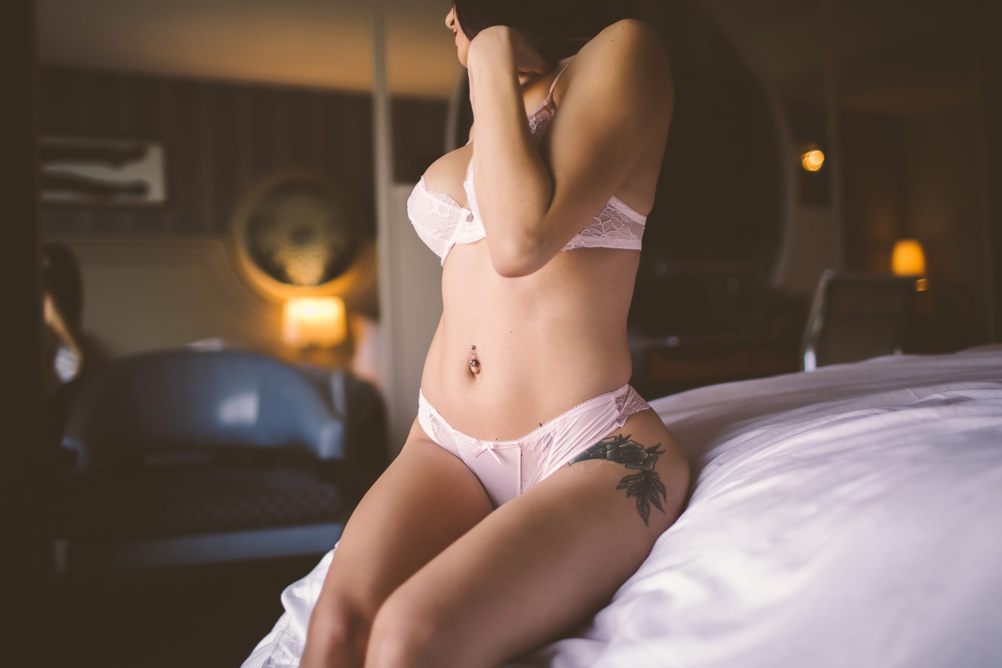 A sexy shot of a model on a hotel bed