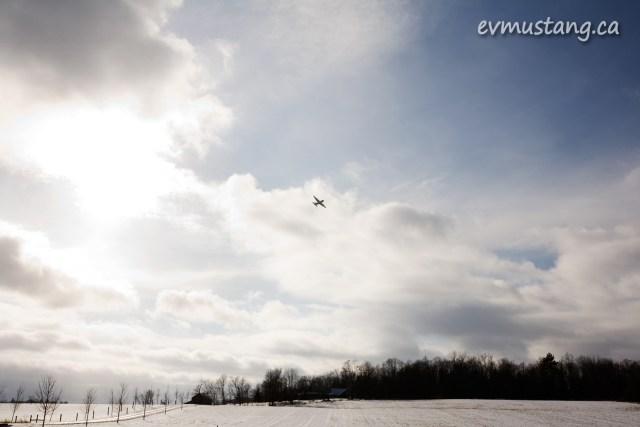 image of a bomber flying over a modern winter landscape