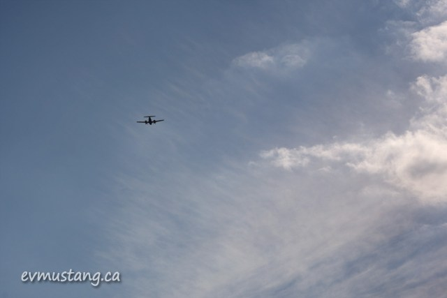 image of airplane silhouetted in clouded sky