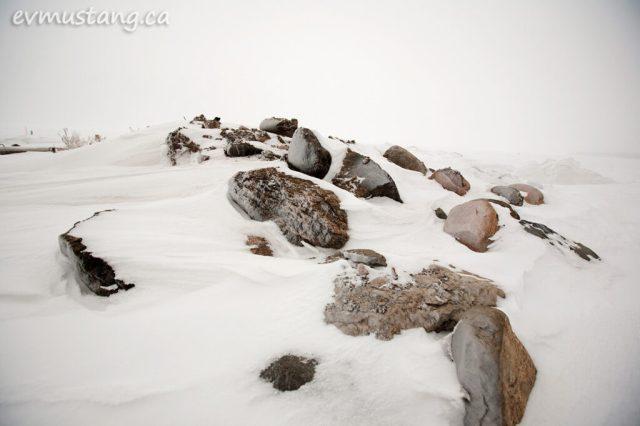 image of granite boulders in bleak snow beside a winter lake