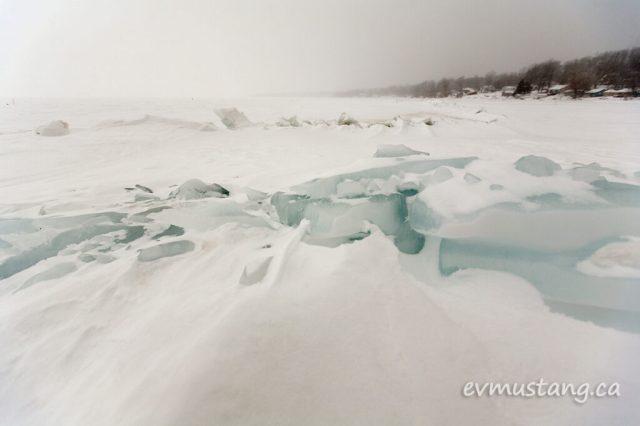 image of blue ice breaks in a bleak lakeside landscape