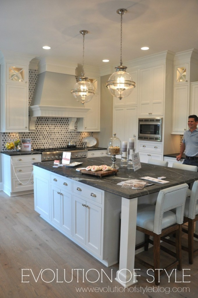 White kitchen with dark countertops and gray barstools