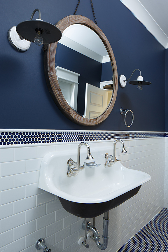 Navy and white bathroom with round mirror